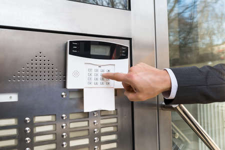 the entering: Close-up Of Businessperson Hand Entering Code In Security System Stock Photo