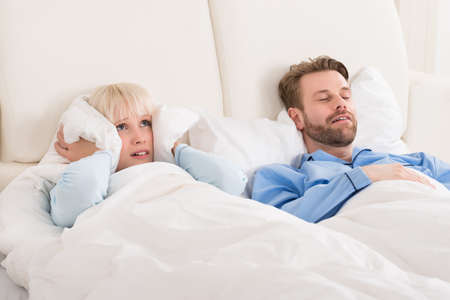 snore: Young Woman Covering Ears While Man Snoring In Bed At Home