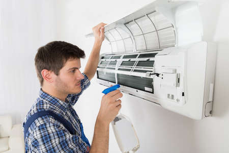 Young Male Technician Cleaning Air Conditioner At Home Reklamní fotografie