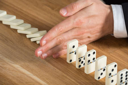 continuity: Close-up Of Young Businessperson Stopping Dominos From Falling On Wooden Desk