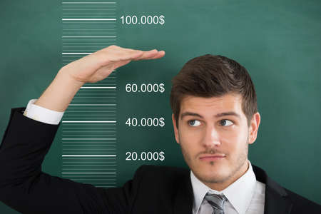 Close-up Of A Young Businessman Comparing His Salary With Profit Archivio Fotografico