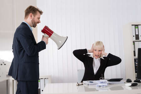 acoso laboral: Protuberancia que grita Al joven empresaria a través del altavoz En Office Foto de archivo