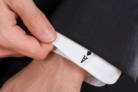 Close-up der Geschäftsmann Hand entfernen Ace-Karte von der Hülse