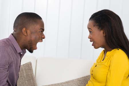 persona enojada: Hombre africano enojado joven gritando en la mujer