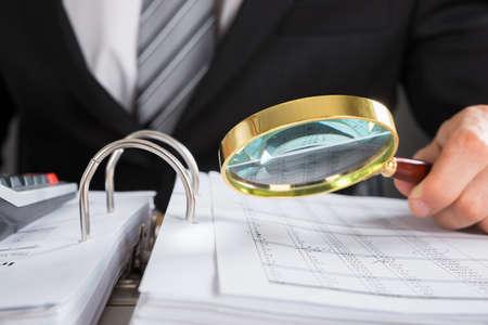 auditoría: Primer plano de la mano joven empresario examinar la factura con la lupa