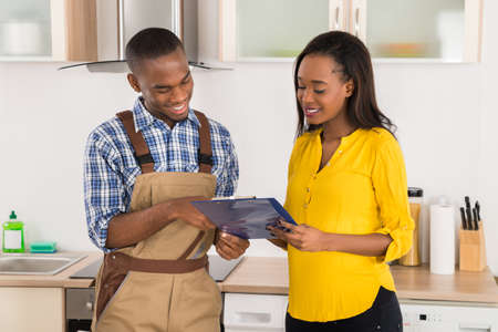 happy customer: Young Happy African Handyman And Woman Looking At Clipboard Stock Photo