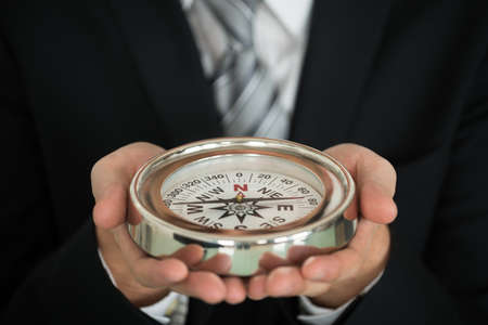 north star: Close-up Photo Of Businessman Hand Holding Compass