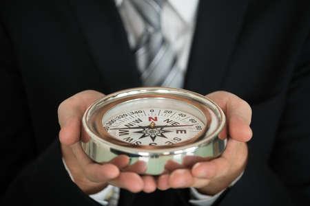 flechas direccion: Primer plano Foto del empresario mano que sostiene el compás Foto de archivo