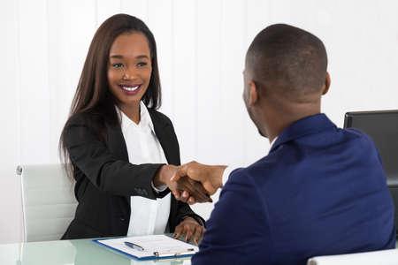 Dos empresarios exitosos afroamericanos estrechar la mano en la Oficina