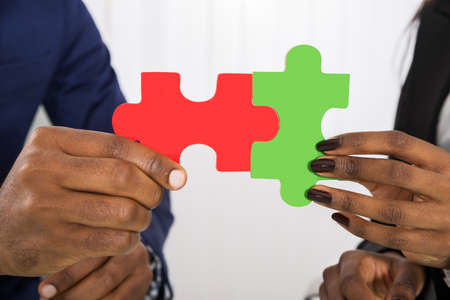 two hands: Close-up Of Man And Woman Holding Puzzle Pieces