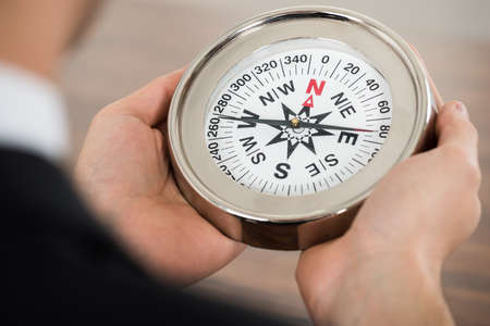 guiding: Close-up Photo Of Businessman Holding Compass In Office