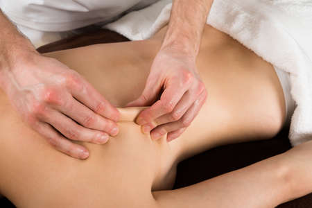 acupressure hands: Close-up Of A Young Woman Receiving Massage From A Massager In A Beauty Spa Stock Photo