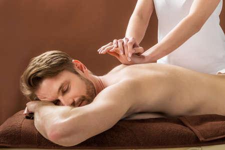 masaje deportivo: Retrato de un hombre joven que recibe masaje posterior en un balneario de la belleza
