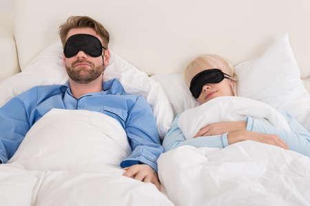 eye mask: Young Couple Sleeping Comfortably On Bed Using Eye Mask Stock Photo