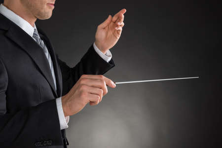 baton: Person Directing With A Conductors Baton On Grey Background