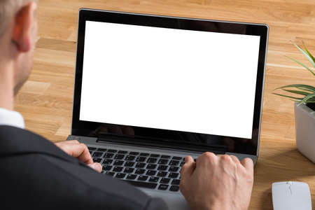blank screen: Close-up Of Businessman Using Laptop With Blank Screen At Desk Stock Photo