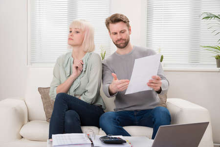 over: Unhappy Couple Having Argument Over Bill At Home