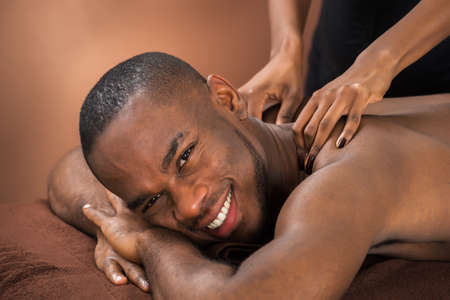 acupressure hands: Close-up Of Happy African Man Receiving Massage Treatment