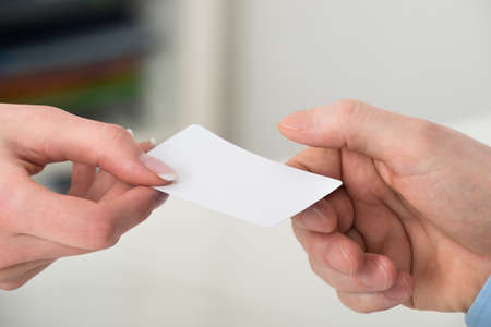 notecard: Close-up Of Two Businesspeople Hand Exchanging Visiting Card In Office Stock Photo