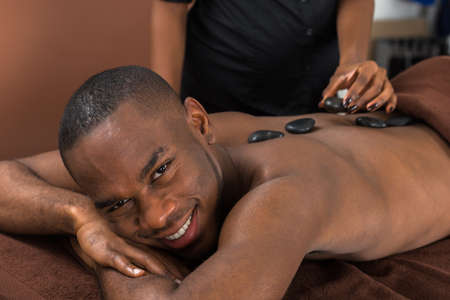African Man Relaxing In A Spa Getting Hot Stone Therapy Stock Photo