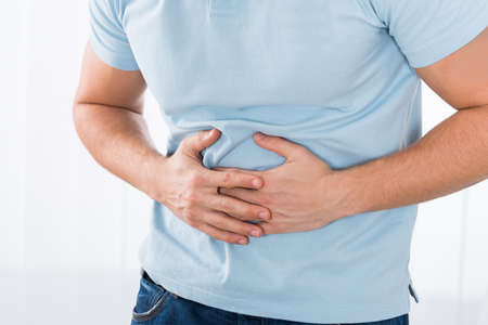 digestive disease: Close-up Of Young Man Suffering From Stomach Ache Standing At Home