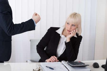dedo apuntando: Primer Del Jefe de culpar Mujer joven empleado de malos resultados en oficina