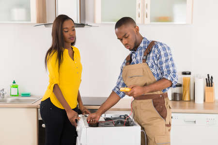 black lady: Young Worker Repairing Washer In Kitchen Room Stock Photo