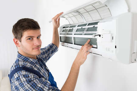 room air: Young Male Technician Repairing Air Conditioner At Home