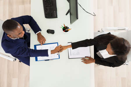 High Angle View Of Two Businesspeople Shaking Hand