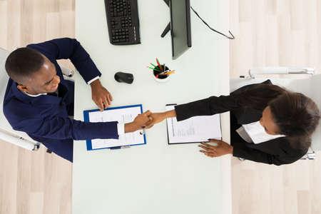 vysoký úhel pohledu: Vysoký úhel pohledu dvou podnikatelů potřesení rukou