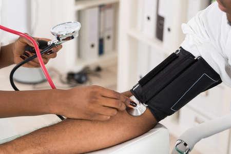 high: Primer plano de medición de la presión arterial de los pacientes con el estetoscopio