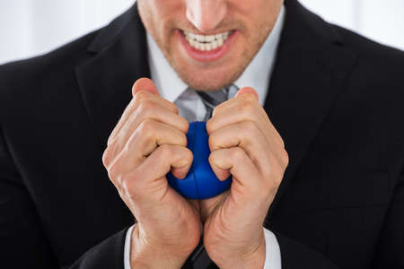 releasing: Close-up Of Businessman Pressing Stress Ball In Office