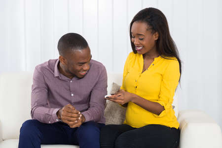 expectant: Young Expectant Couple Sitting On Sofa Looking At Pregnancy Test