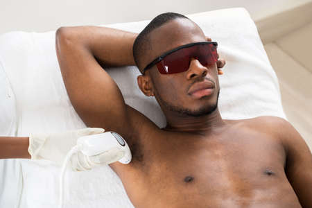 male hair: Therapist Giving Laser Epilation Treatment On Young African Mans Armpit