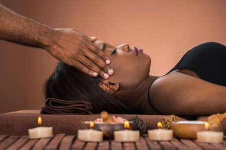 Mujer africana relajada joven que recibe el masaje en el spa de la frente Foto de archivo