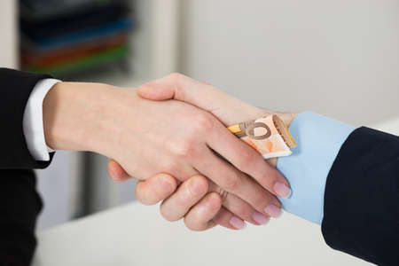 bribing: Close-up Of Businessperson Bribing Partner While Shaking Hand In Office