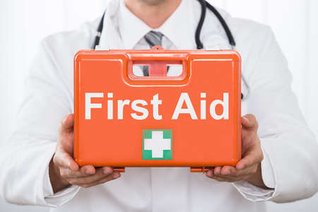 first aid box: Close-up Of Young Male Doctor Hand Holding First Aid Kit Box In Clinic