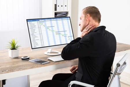 suffer: Young Businessman Suffering From Neck Ache While Using Computer At Office