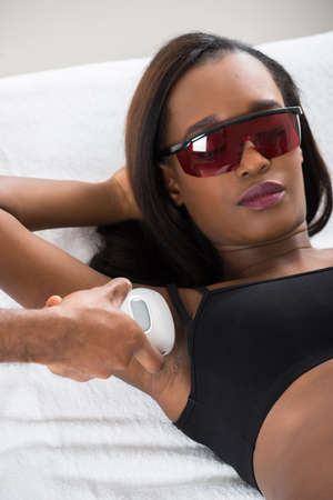 armpit hair: Therapist Removing Hair Of Young African Womans Armpit With Epilator Stock Photo