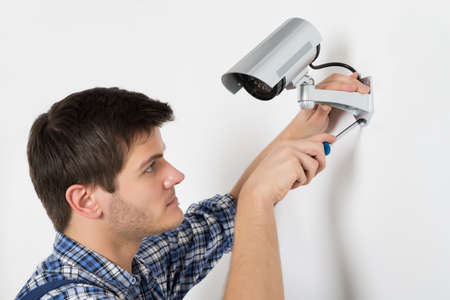 man with camera: Close-up Of Technician Adjusting CCTV Camera On Wall