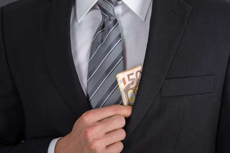 putting money in pocket: Close-up Of Businessman Putting Bribe Money In Suit Pocket Stock Photo