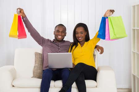 ショッピング バッグと自宅のソファに座ってノート パソコンと若いアフリカ カップル