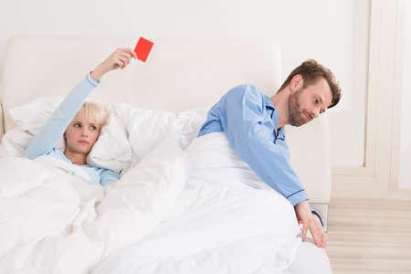 Infeliz mujer joven que muestra la tarjeta amarilla contra el hombre en la cama Foto de archivo