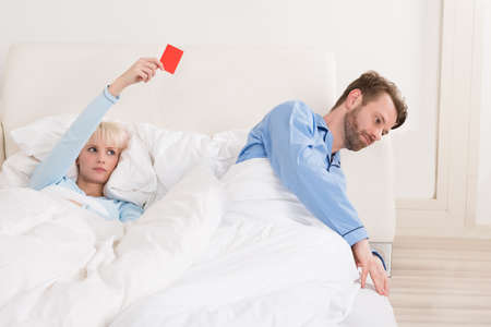 Unhappy Young Woman Showing Red Card To Man In Bed Stock Photo