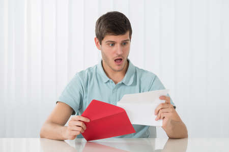 young man portrait: Portrait Of Surprised Young Man Looking At Letter Stock Photo