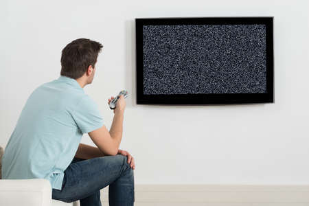 no signal: Man Sitting On Sofa In Front Of Television With No Signal Stock Photo