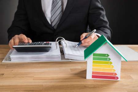 Geschäftsmann Calculate Financial Data mit House Model Showing Energieeffizienz-Rate auf Schreibtisch