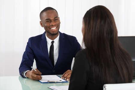 Hombre de entrevistar a un solicitante hembra joven en Office Manager