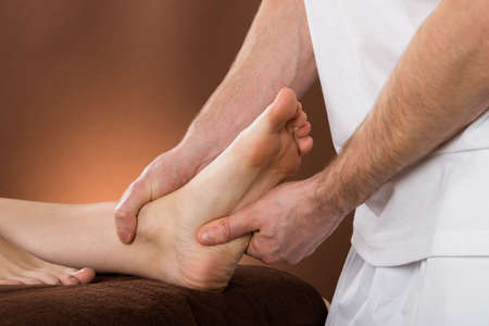 acupressure hands: Close-up Of A Woman Receiving Foot Massage From A Male Therapist At A Beauty Spa