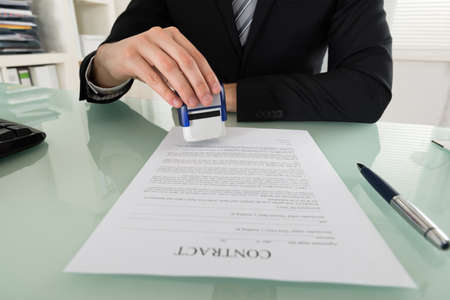 stamper: Close-up Of Businessman Hand Using Stamper On Document Stock Photo